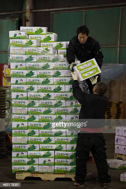 Workers move boxes of green pumpkin at Garak Market operated by Seoul AgroFisheries Food Corp in Seoul South Korea on Wednesday Jan 15 2014 South...