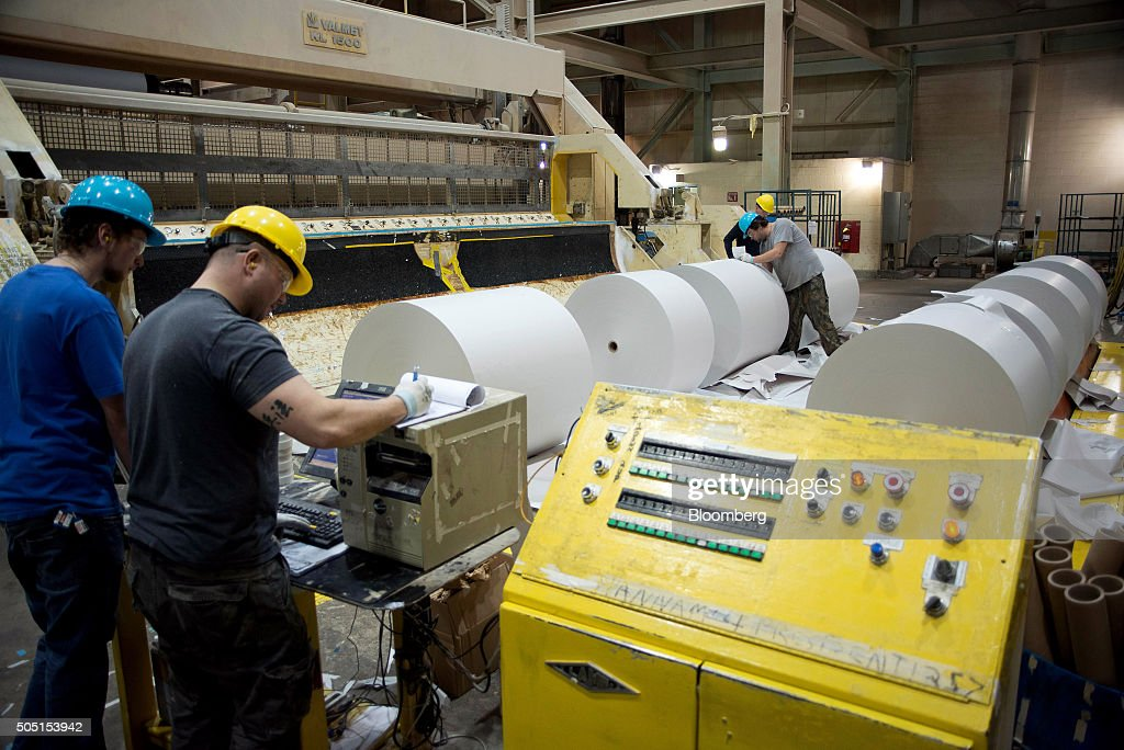 Workers move finished rolls of newsprint paper off the production line at the Resolute Forest Products mill in Thunder Bay Canada Ontario on Thursday...