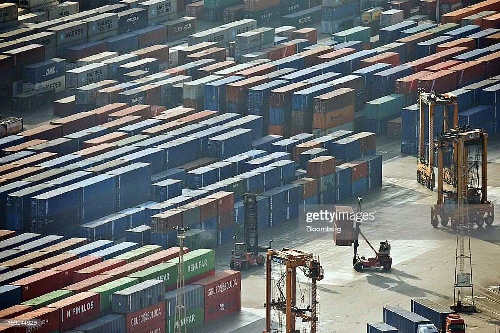 Workers move shipping containers around the dockside at Barcelona port in Barcelona, Spain, on Thursday, Jan. 10, 2013. Spanish exports grew the least in five months in September as the euro area relapsed into a recession and the region's fourth-largest economy continued to contract. Photographer: David Ramos/Bloomberg via Getty Images