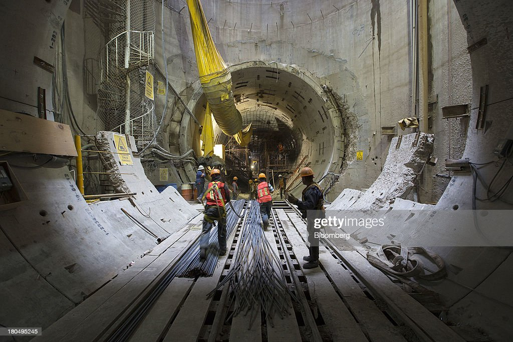 Workers move steel rods inside the Tunnel Emisor Oriente (TEO), or Eastern Discharge Tunnel, during construction of the 38 mile (62km) underground wastewater treatment tunnel in Mexico City, Mexico, on Thursday, Sept. 12, 2013. The tunnel, which is expected to be completed in 2014, will boost Mexico City's drainage capacity to help prevent flooding during rainy season and the over-exploitation of groundwater resources. The project is being managed by Mexico's National Water Commission, Conagua. Photographer: Susana Gonzalez/Bloomberg via Getty Images