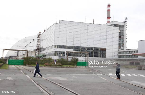 Workers near new protective shelter over the nuclear reactor Unit 4 at Chernobyl nuclear power plant are seen during the 31st anniversary of...