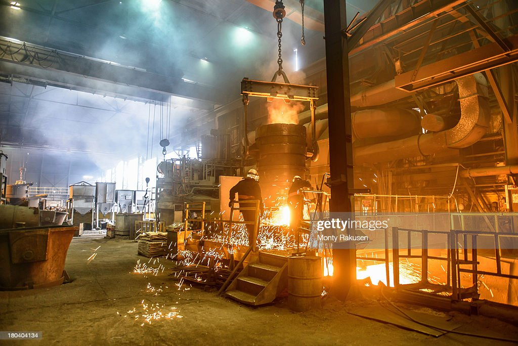 Workers next to furnace pouring molten steel in industrial foundry