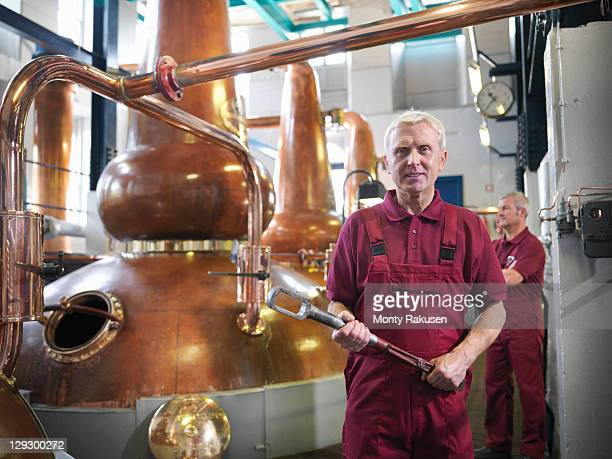 Workers next to whisky stills in distillery