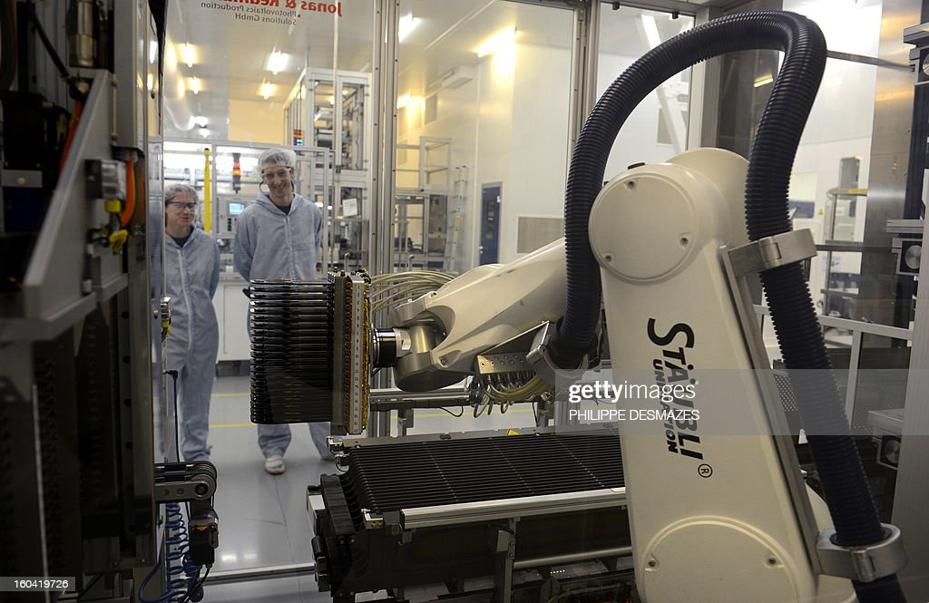 Workers observe a photovoltaic unit at the French solar panel maker PhotoWatt factory in Bourgoin-Jallieu, near Lyon, on January 31, 2013.