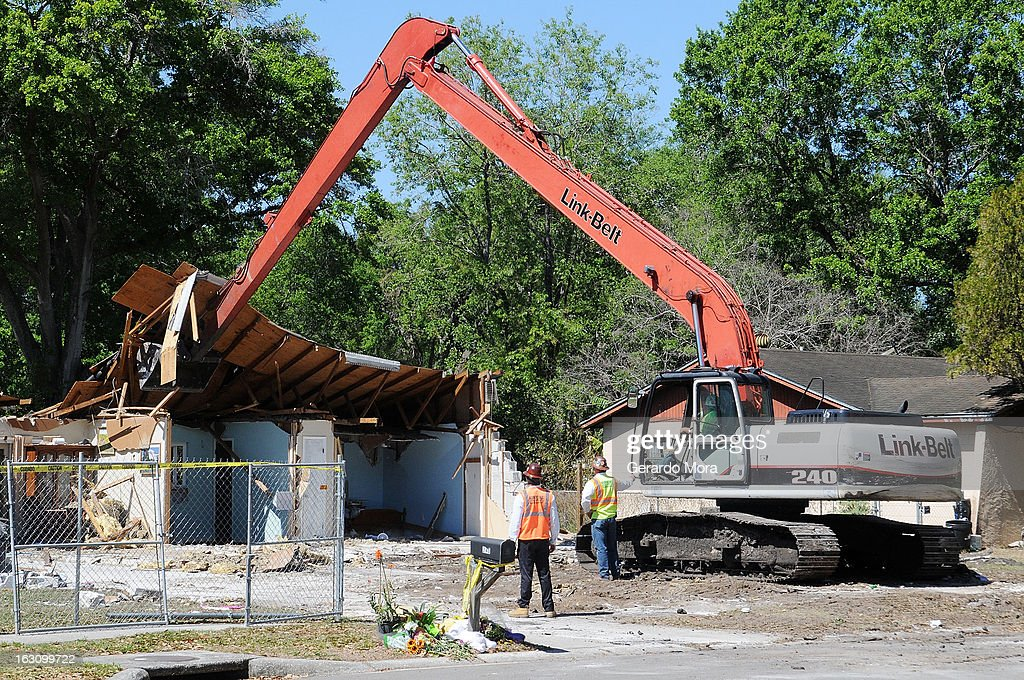 Workers observe the demolition of the home where a sinkhole swallowed Jeffrey Bush on March 4, 2013 in Seffner, Florida. Jeff Bush, presumed dead after a sinkhole, estimated at 60 feet deep, opened under his bedroom while he was sleeping in the home. Demolition crews are working to raze the house, recover possessions, and stabilize the now-shaky ground.