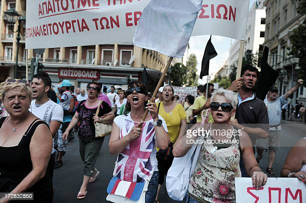 Workers of a Greek bakery products plant which declared bankrupcy shout slogans as they march in central Athens on July 5 demanding measures that...