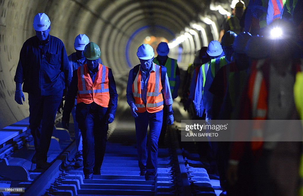 Workers of French company Alstom walk in a tunnel during the visit of French Junior Minister for the Social Economy, Benoit Hamon (not in frame) in Caracas on November 25, 2012. Venezuela and France signed seven cooperation agreements in areas such as manufacturing, mining, science and tourism during Hamon's visit to Caracas. AFP PHOTO/JUAN BARRETO