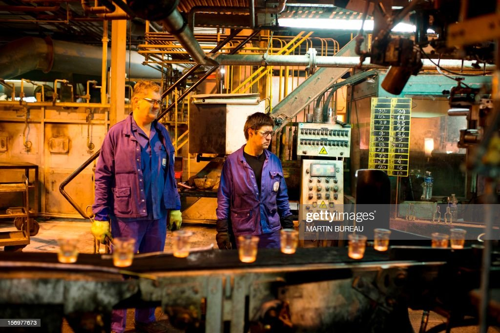 Workers of French manufacturer of glassware Duralex supervise a production line, on November 26, 2012 at the factory in La Chapelle-Saint-Mesmin. AFP PHOTO MARTIN BUREAU