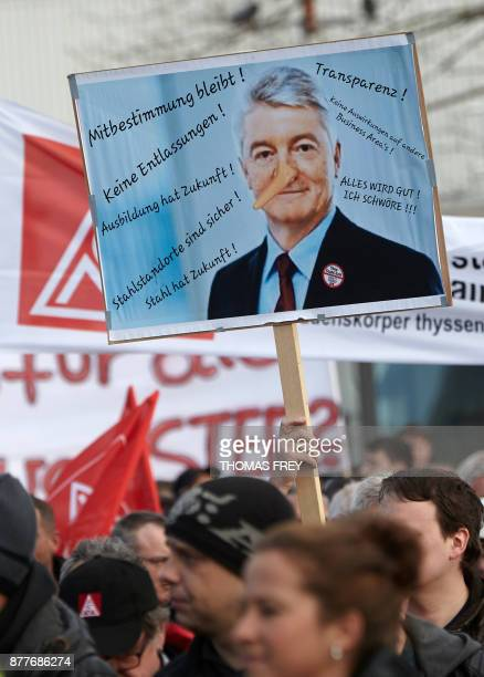 Workers of German heavy industry giant ThyssenKrupp hold up a sign depicting chairman of ThyssenKrupp Heinrich Hiesinger with a long nose on November...