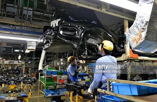 Workers of Japan's auto maker Fuji Heavy Industries known as Subaru brand assemble suspensions to the vehicle at the company's Gunma Yajima Plant at...