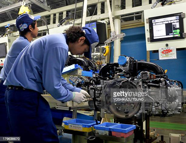 Workers of Japan's auto maker Fuji Heavy Industries known as Subaru brand assemble a flatfour engine at the company's Gunma Oizumi plant at Oizumi...