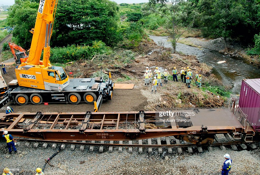Workers of JR Hokkaido continue the restoration work as a goods train derailment on August 17, 2013 in Yakumo, Hokkaido, Japan. Train operation between Yakumo and Mori has been suspended due to a landslide triggered by a torrential rain washed the enbankment, hit 'bon' holidaymakers.