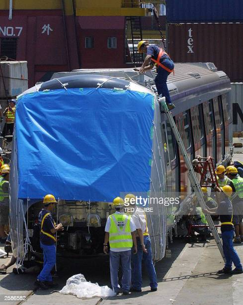 Workers of Kowloon Canton Railway inspect one of its new train cars after it was unloaded at the company''s freight yard in Hong Kong 26 September...