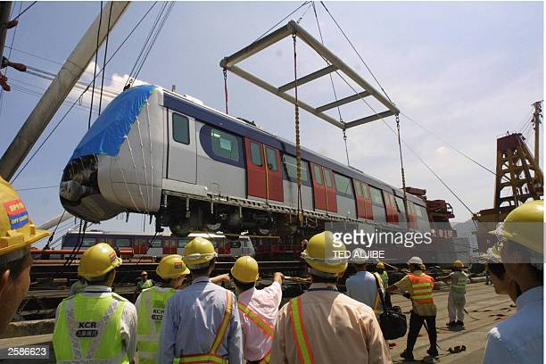 Workers of Kowloon Canton Railway watch as one of its new train cars after it was unloaded at the company''s freight yard in Hong Kong 26 September...