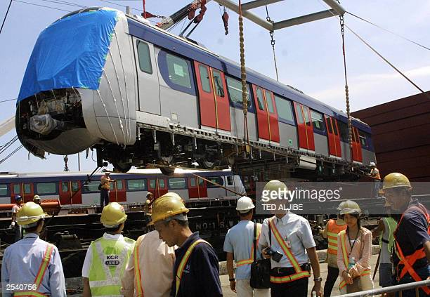 Workers of Kowloon Canton Railway watch as one of the new train cars is unloaded at the company's freight yard in Hong Kong 26 September 2003 The new...