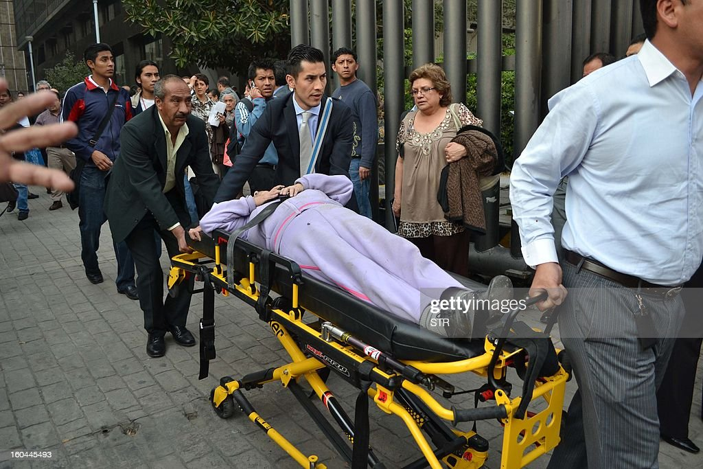 Workers of Pemex help to their partners outside the headquarters of state-owned Mexican oil giant Pemex in Mexico City on January 31, 2013, following a blast inside the building. An explosion rocked the skyscraper, leaving up to now 14 dead and 100 injured, as a plume of black smoke billowed from the 54-floor tower, according to official sources.