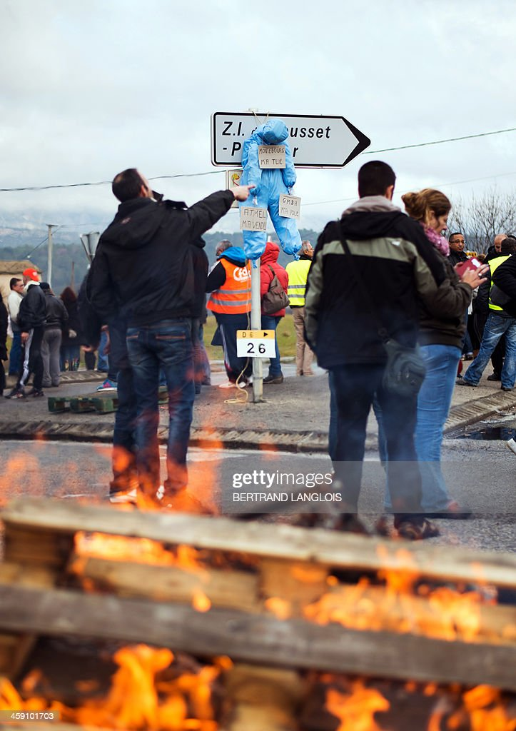 Workers of semiconductor manufacturer LFoundry block the access to the Industrial Zone in Rousset, near Aix-en-Provence, southern France, on December 23, 2013, after trade unions announced that a court had ordered a judicial liquidation of their factory. Over 670 jobs are at risk if the factory closes and approximately 400 workers took part in the protest and blocade of the Rousset industrial zone, as French Minister for Industrial Renewal Arnaud Montebourg prepared to receive a delegation of workers in Paris today.