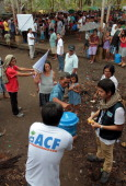 Workers of Spanish based ACF International distribute hygiene kits to typhoon affected residents in coastal village devastated by super typhoon Bopha...