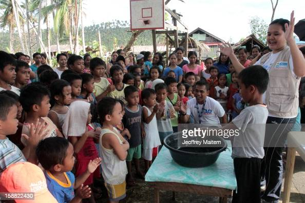 Workers of Spanish based ACF International teach children proper washing of hands in coastal village devastated by super typhoon Bopha on December 30...