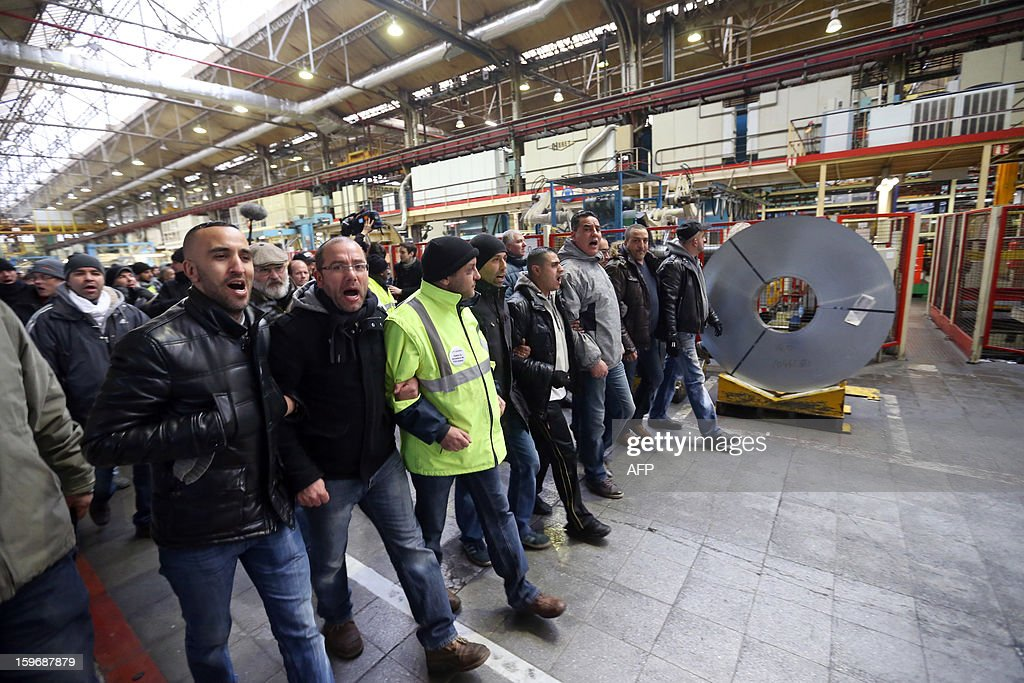 Workers of the Aulnay's French automobile constructor PSA Peugeot Citroen plant demonstrate in the Saint-Ouen's PSA factory after entered the plant illegally through a hole in the wall on January 18, 2013, northern Paris. Aulnay's workers are on strike to protest against the closure of their factory. The company was rescued last October with a state guarantee of 7.0 billion euros ($9.0 billion) for its banking and credit arm, and is locked in a restructuring programme involving a plant closure and the loss of 8,000 jobs. SAMSON