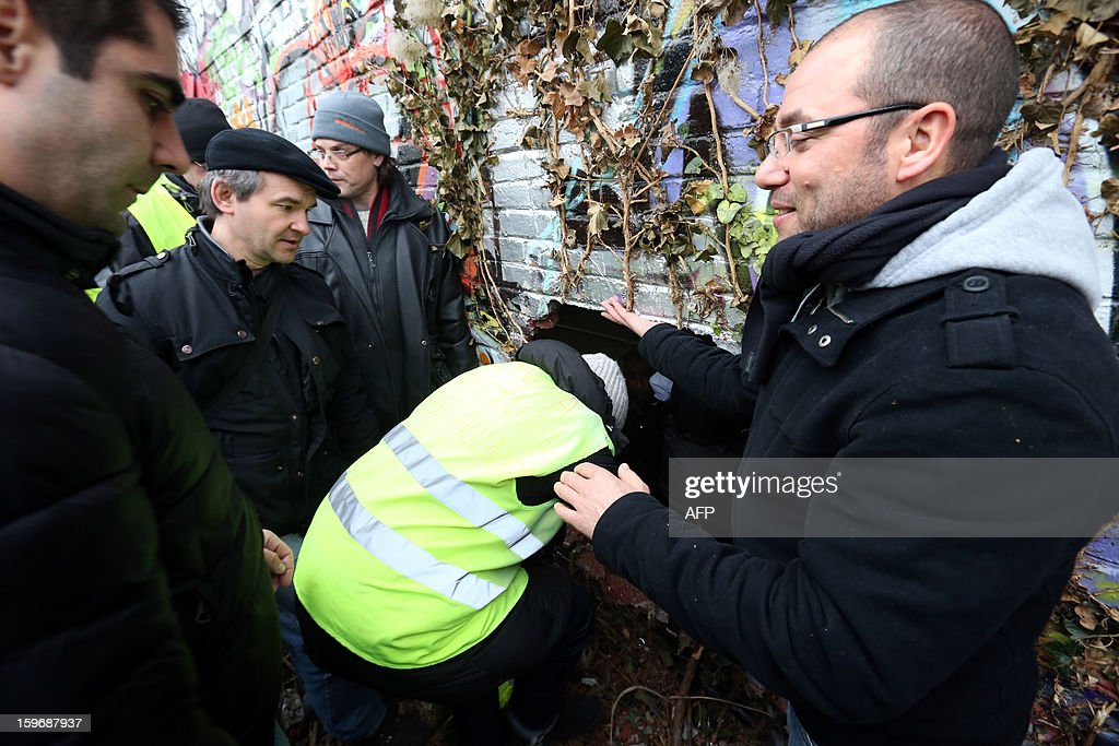 Workers of the Aulnay's French automobile constructor PSA Peugeot Citroen plant enter illegally through a hole in the wall of the Saint-Ouen's PSA factory on January 18, 2013, northern Paris. Aulnay's workers are on strike to protest against the closure of their factory. The company was rescued last October with a state guarantee of 7.0 billion euros ($9.0 billion) for its banking and credit arm, and is locked in a restructuring programme involving a plant closure and the loss of 8,000 jobs. SAMSON