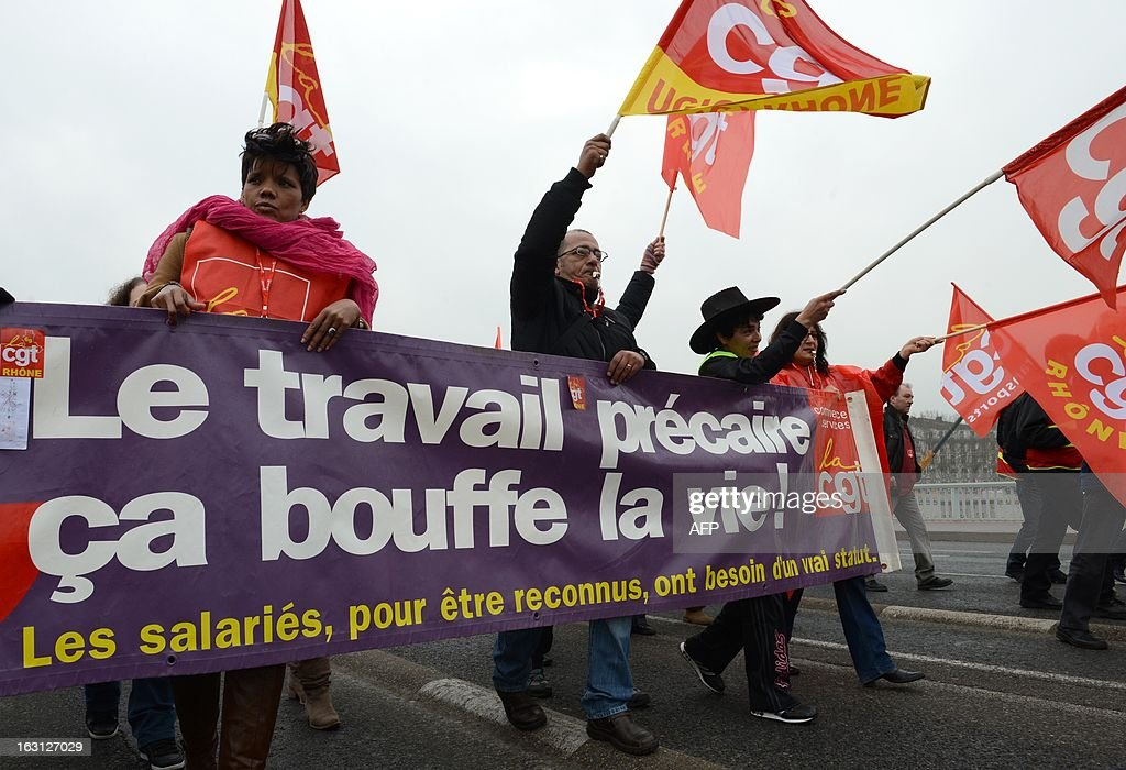 Workers of the CGT trade union wave union flags on March 5, 2013 in Lyon, southeastern France, during a demonstration called by CGT and fellow union FO to protest against last January 11's interbranch agreements between several workers' unions and the French employers' association Medef, on employment's safeguard. The government will discuss the agreement in the March 6 cabinet meeting.