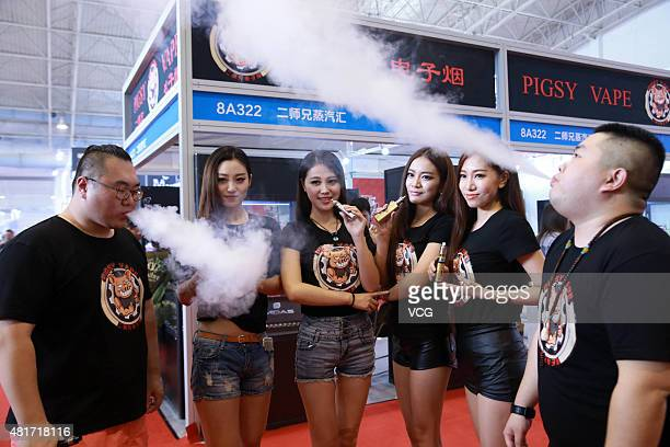 Workers of the exhibition smoke electronic cigarettes during Beijing International Vapor Distribution Alliance Expo at China International Exhibition...
