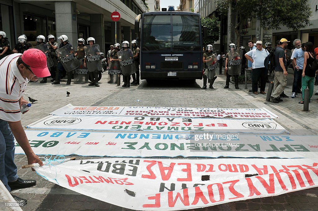 Workers of the Hellenic Defence Systems and Vehicle Industry lay banners in front of the Finance ministry, protected by police forces, during a protest in Athens on July 11, 2013. Public-sector federation Adedy called a work stoppage in Athens against government plans to dismiss public servants, contained in an omnibus bill before parliament, and a protest rally in central Athens.