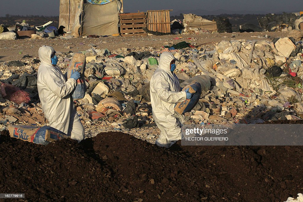 Workers of the Mexican Secretariat of Agriculture, Livestock, Rural Development, Fisheries, & Nutrition water chemical and lime on infected chicken manure called 'gallinaza' in a garbage dump in Dolores Hidalgo, Guanajuato State, Mexico on February 26, 2013. The Mexican government declared a national animal health emergency in the states of Guanajuato, Jalisco and Aguascalientes, where so far 18 farms are infected and more than two million birds were killed. AFP PHOTO/Hector Guerrero