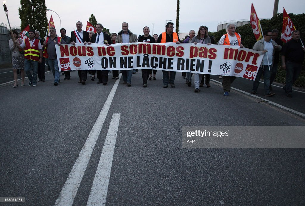 Workers of the Petroplus oil refinery in the Petit-Couronne hold a banner reading 'We are not dead - We won't let go !' as they take part in a protest march on May 7, 2013. Between 350 to 400 workers of the refinery which is shutting down its operations took part in the march. AFP PHOTO / CHARLY TRIBALLEAU