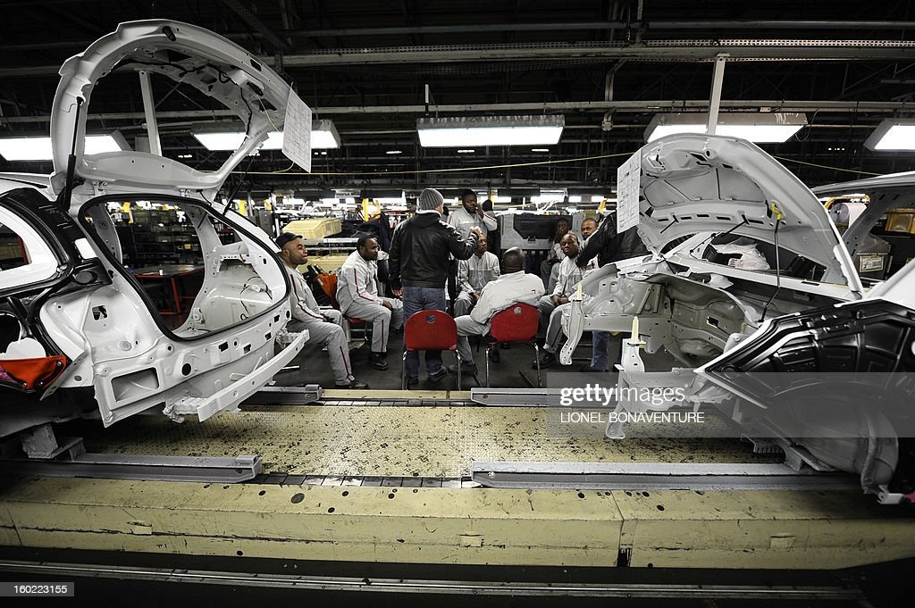 Workers of the PSA Peugeot Citroen carmaker plant of Aulnay-sous-Bois, a Paris' suburb, gather for the morning briefing on January 28, 2013 at the plant.