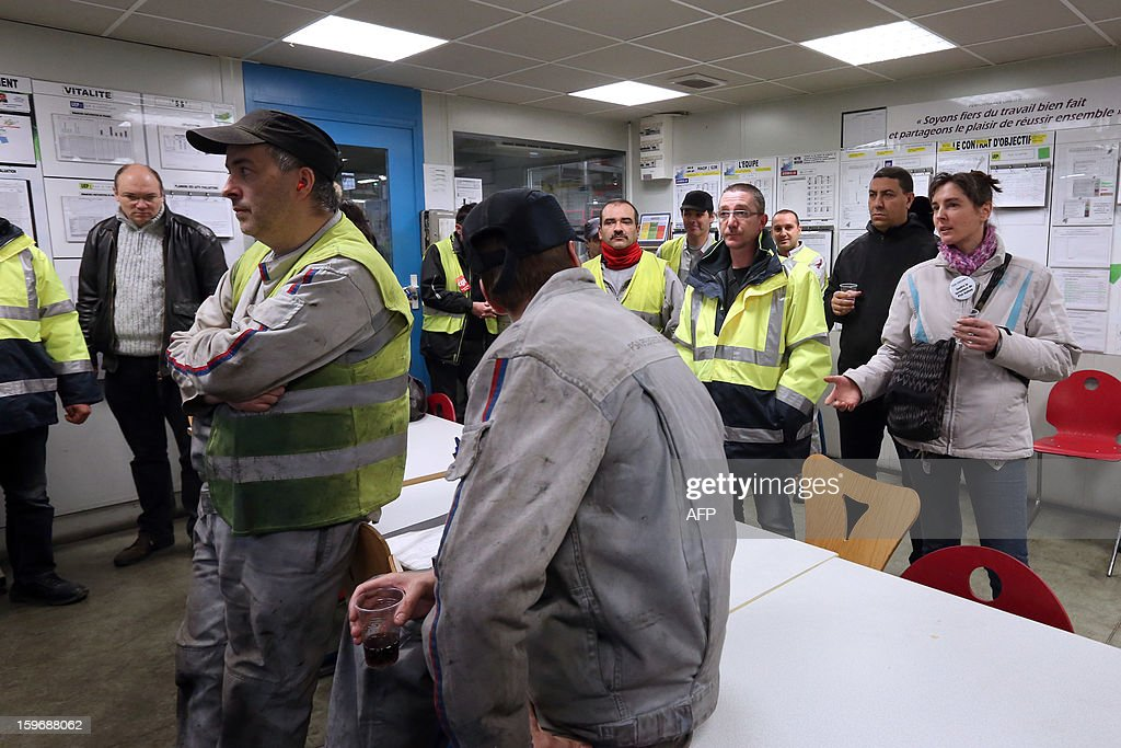 Workers of the Saint-Ouen's French automobile constructor PSA Peugeot Citroen plant listen to one of the CGT unionised workers (R) of the Saint-Ouen's PSA factory who entered illegally through a hole in the wall on January 18, 2013, northern Paris. Aulnay's workers are on strike to protest against the closure of their factory. The company was rescued last October with a state guarantee of 7.0 billion euros ($9.0 billion) for its banking and credit arm, and is locked in a restructuring programme involving a plant closure and the loss of 8,000 jobs. SAMSON