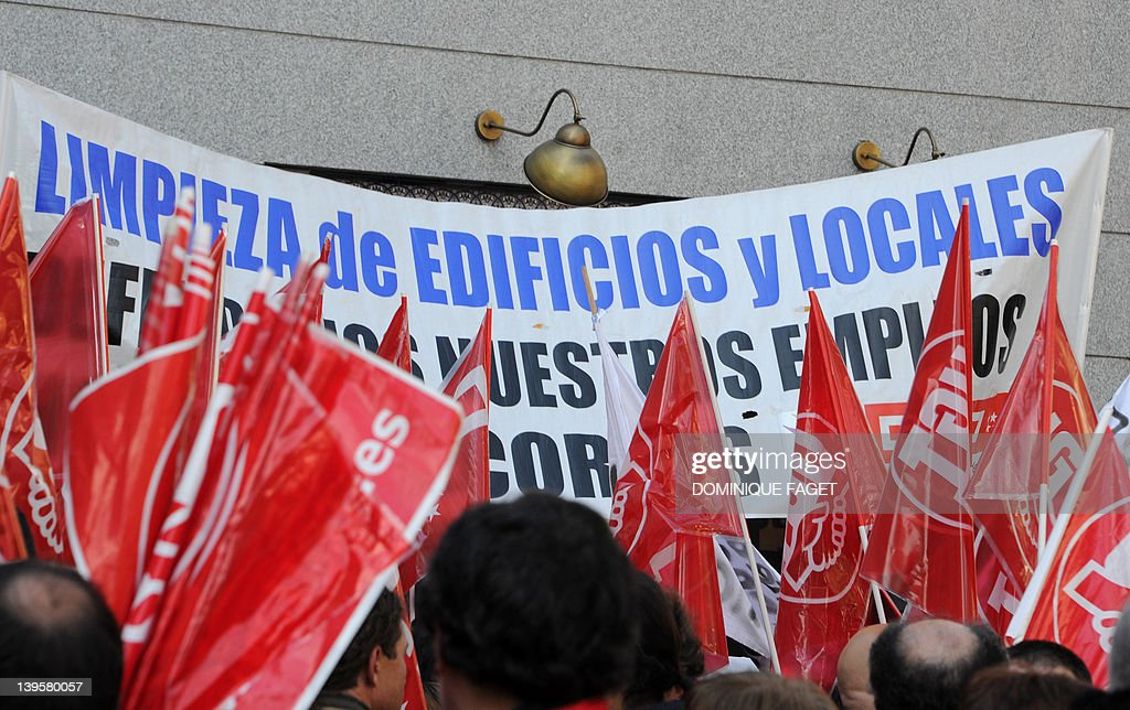 Workers of the service industry hold a banner reading 'Cleaning of buildings and premises. Let's defend our jobs. Against cuts' during a demonstration on February 23, 2012 in Madrid. Since Spain's Prime Minister Mariano Rajoy's government took power in December 2011 it has announced billions of euros in planned savings through budget cuts, tax hikes and an anti-tax fraud drive, ledding to several demonstrations against budget cuts. AFP PHOTO / DOMINIQUE FAGET