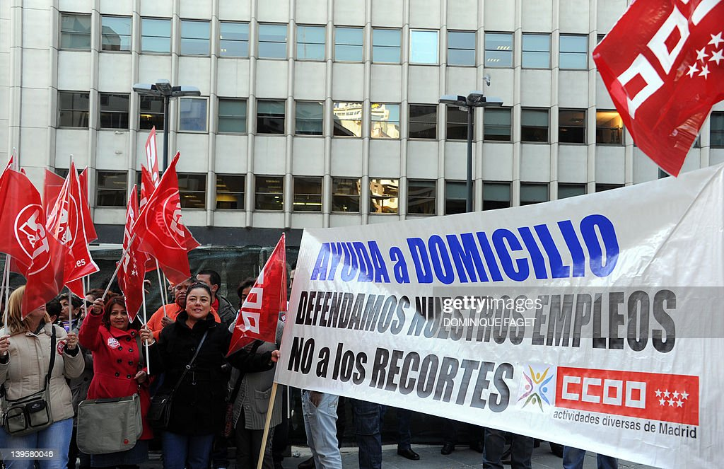 Workers of the service industry hold a banner reading 'Home assistance. Let's defend our jobs. Against cuts' during a demonstration on February 23, 2012 in Madrid. Since Spain's Prime Minister Mariano Rajoy's government took power in December 2011 it has announced billions of euros in planned savings through budget cuts, tax hikes and an anti-tax fraud drive, ledding to several demonstrations against budget cuts.