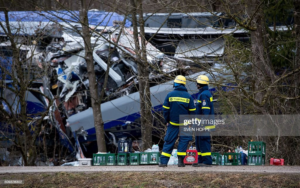 Workers of the Technisches Hilfswerk (THW) technical relief unit stand at the site of a train accident near Bad Aibling, southern Germany, on February 10, 2016. Two Meridian commuter trains operated by Transdev on February 9, 2016 collided head-on near Bad Aibling, around 60 kilometres (40 miles) southeast of Munich, killing at least ten people and injuring around 100, police said. / AFP / dpa / Sven Hoppe / Germany OUT