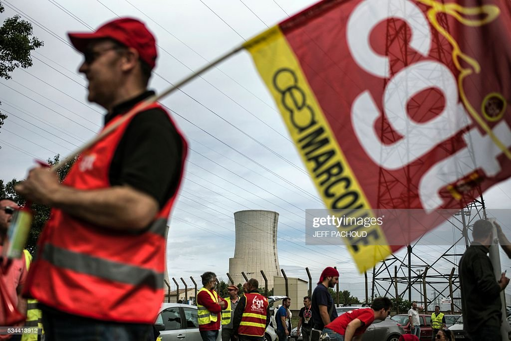 Workers of the Tricastin nuclear power plant protest at the entrance of the site on May 26, 2016 in Saint-Paul-Trois-Chateaux, during a protest against controversial labour market reforms that has already severely disrupted fuel supplies. With two weeks until France hosts the Euro 2016 football championships, the country has been paralysed by a series of transport strikes and fuel shortages that has heaped pressure on the deeply unpopular Socialist government. / AFP / JEFF