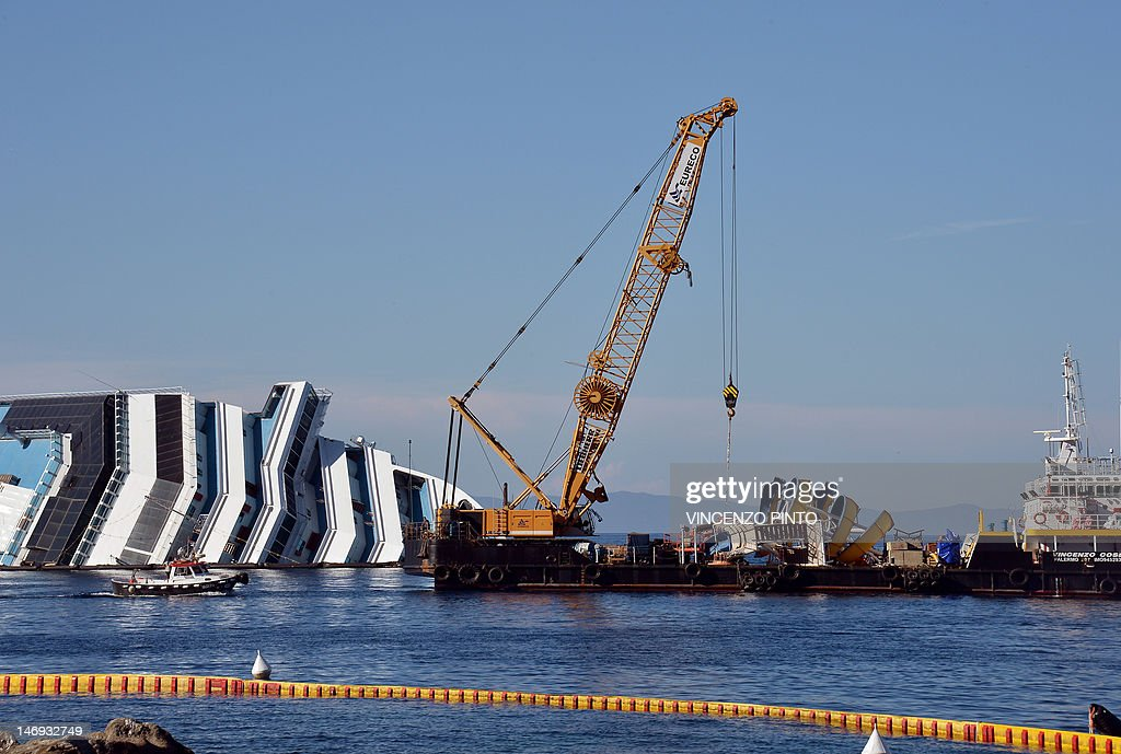 Workers of the U.S. firm Titan Salvage and Italian firm Micoperi take off the swimming pool slide from the Costa Concordia upper deck near the harbour of Giglio Porto on June 23, 2012. Salvage crews began preliminary work this week on preparations to refloat the half-submerged Costa Concordia cruise liner in what is set to be the biggest ever operation of its kind. The cruise liner, operated by Carnival Corp's Costa Cruises unit, capsized off the Tuscan island of Giglio after hitting rocks on January 13. At least 30 people died and two are still unaccounted for.