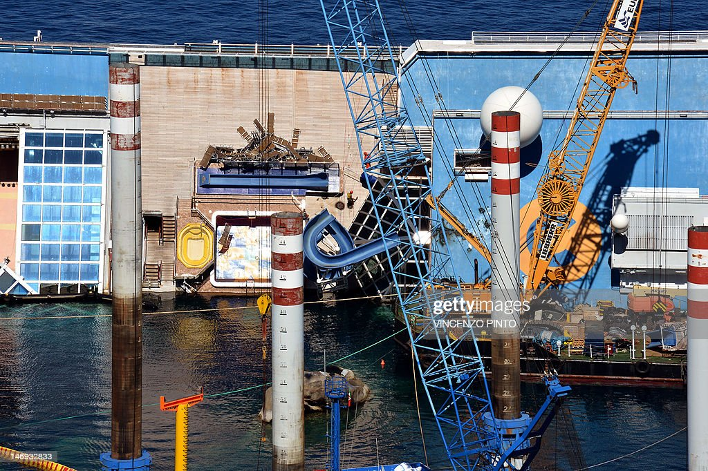 Workers of the U.S. firm Titan Salvage and Italian firm Micoperi take off the swimming pool slide from the Costa Concordia upper deck near the harbour of Giglio Porto on June 23, 2012. Salvage crews began preliminary work this week on preparations to refloat the half-submerged Costa Concordia cruise liner in what is set to be the biggest ever operation of its kind. The cruise liner, operated by Carnival Corp's Costa Cruises unit, capsized off the Tuscan island of Giglio after hitting rocks on January 13. At least 30 people died and two are still unaccounted for. AFP PHOTO/ VINCENZO PINTO