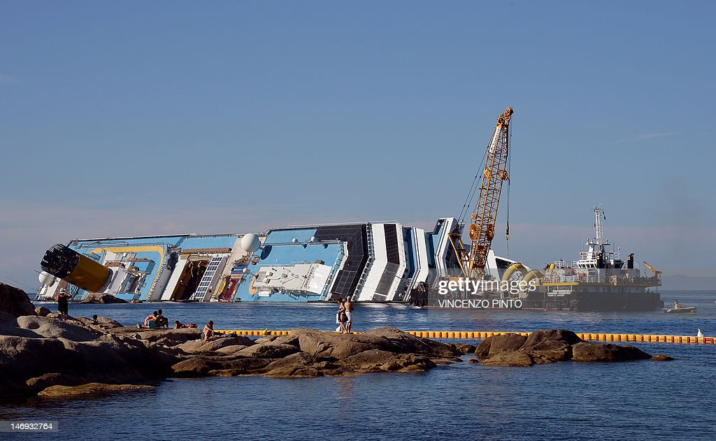 Workers of the U.S. firm Titan Salvage and Italian firm Micoperi work on salvaging the the Costa Concordia, near the harbour of Giglio Porto on June 23, 2012. Salvage crews began preliminary work this week on preparations to refloat the half-submerged Costa Concordia cruise liner in what is set to be the biggest ever operation of its kind. The cruise liner, operated by Carnival Corp's Costa Cruises unit, capsized off the Tuscan island of Giglio after hitting rocks on January 13. At least 30 people died and two are still unaccounted for.