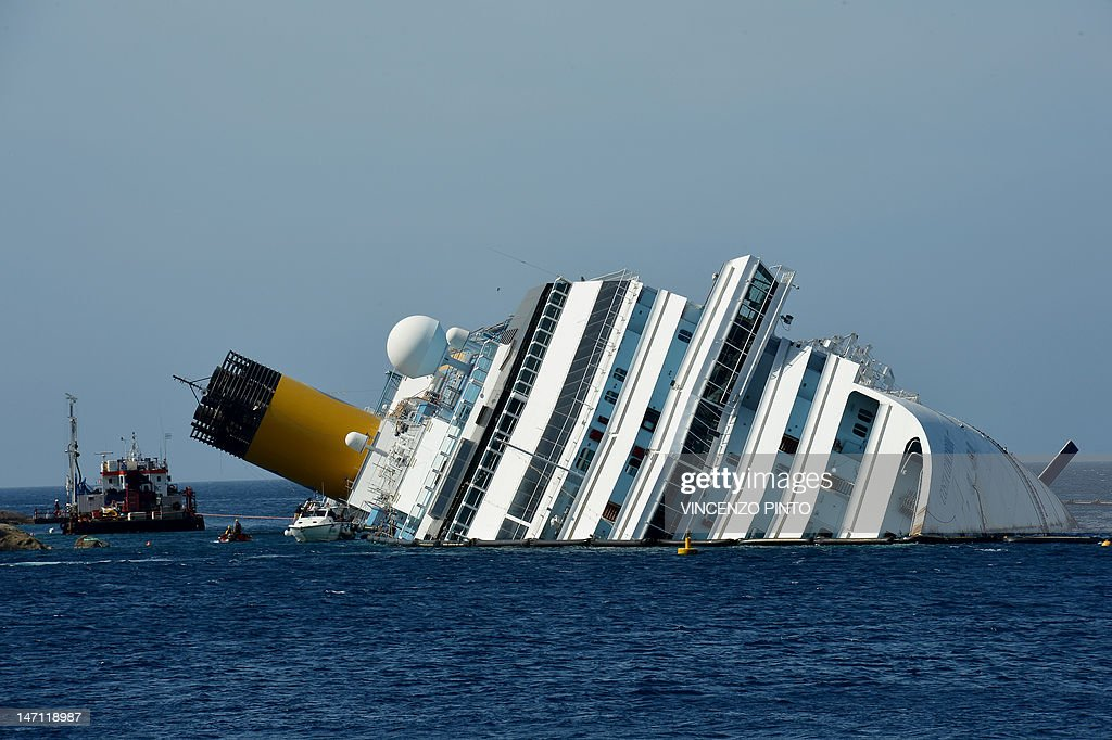 Workers of the US firm Titan Salvage and Italian firm Micoperi work on the stranded Costa Concordia cruise ship near the harbour of Giglio Porto on June 25, 2012. Salvage crews began preliminary work this week on preparations to refloat the half-submerged Costa Concordia cruise liner in what is set to be the biggest ever operation of its kind. The cruise liner, operated by Carnival Corp's Costa Cruises unit, capsized off the Tuscan island of Giglio after hitting rocks on January 13. At least 30 people died and two are still unaccounted for.