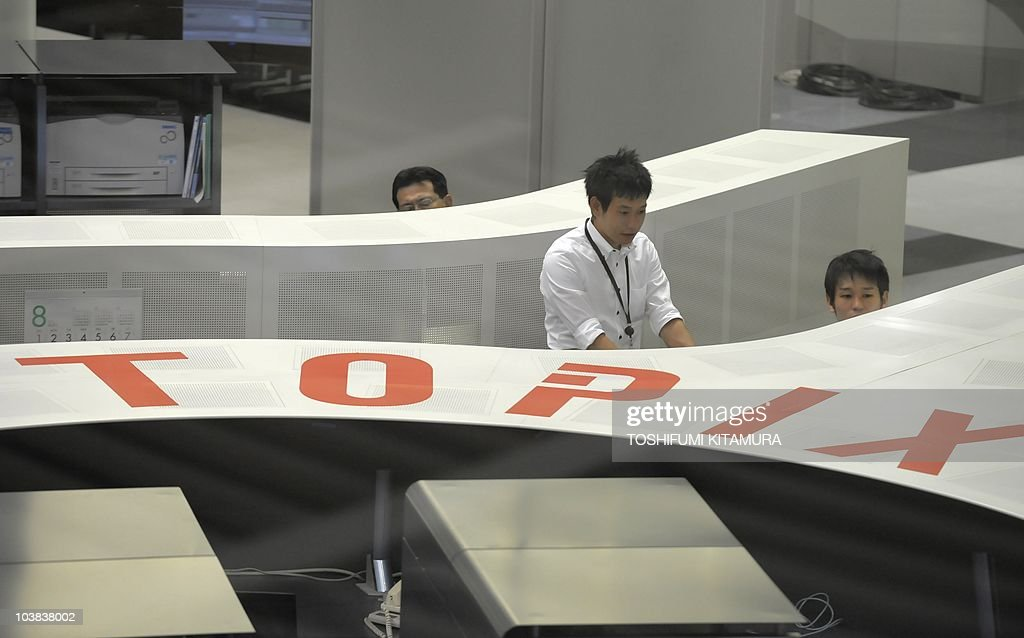Workers of Tokyo Stock Exchange monitor the computer trading at the TSE in Tokyo on August 30 2010 TSE's Nikkei index rose 27433 points or 305...