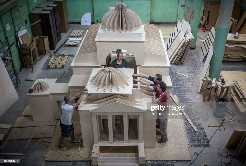 Workers of Tryktrak carpentry workshop fit part of the roof as they are finishing a 1:10 scale model of the largest synagogue in pre-war Warsaw, Great Synagogue in Warsaw, on May 12, 2013. The model will be installed on the place near the original location, on May 16, 2013 - 70 years after it was destroyed during World War II Warsaw Ghetto liquidation. AFP PHOTO WOJTEK RADWANSKI