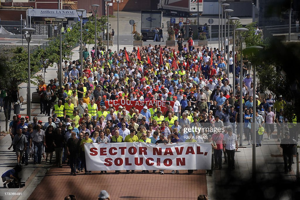 Workers of Zamakona and La Naval shipyards hold a banner reading 'Shipyards, solution' as they take part in a protest against the repayment of state aids by Spanish shipbuilders in the Northern Spanish Basque village of Sestao, on July 11, 2013. Brussels will decide by July 17 if the roughly three billion euros (4.0 billion USD) in state aid which Spanish shipbuilders received between 2005 and 2011 were unauthorised and if they will have to pay the money back. Unions have called for a day of protest and strikes on July 11 when European Union's commissioner for competition, Joaquin Almunia, will meet with representatives of Spanish shipbuilders in Brussels. AFP PHOTO/ RAFA RIVAS