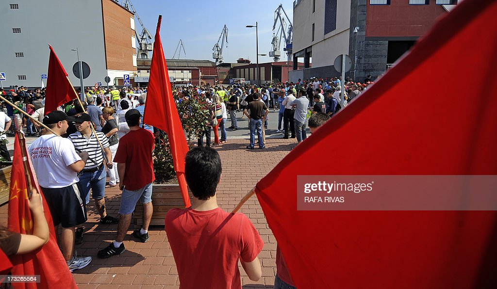 Workers of Zamakona and La Naval shipyards holding red flags take part in a protest against the repayment of state aids by Spanish shipbuilders in the Northern Spanish Basque village of Sestao, on July 11, 2013. Brussels will decide by July 17 if the roughly three billion euros (4.0 billion USD) in state aid which Spanish shipbuilders received between 2005 and 2011 were unauthorised and if they will have to pay the money back. Unions have called for a day of protest and strikes on July 11 when European Union's commissioner for competition, Joaquin Almunia, will meet with representatives of Spanish shipbuilders in Brussels.