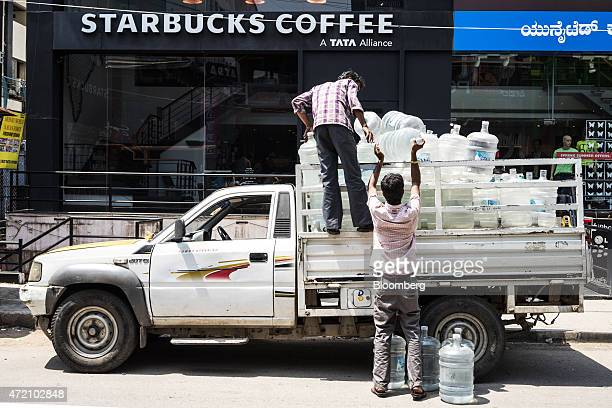 Workers offload water bottles from a pickup truck outside a Starbucks Coffee 'A Tata Alliance' store operated by Tata Starbucks Ltd in the Brigade...