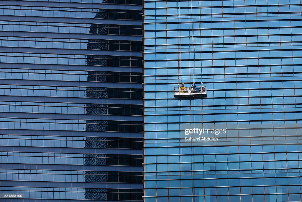 Workers on a gondola lift clean the facade of the Marina Bay Financial Centre Tower on May 26, 2016 in Singapore.