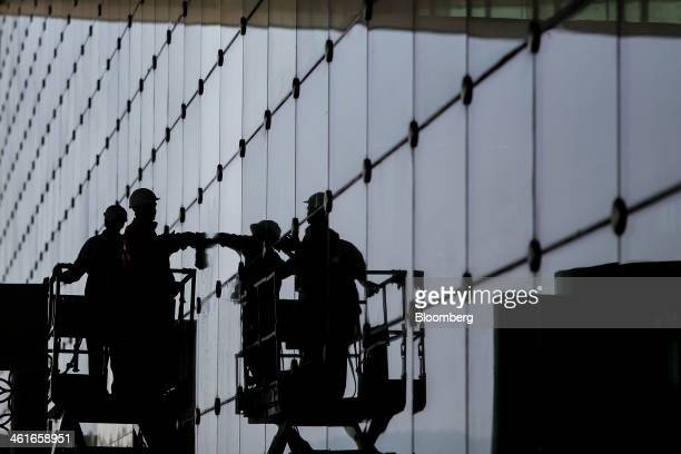 Workers on a mobile platform are reflected as they clean a glass exterior wall of the newly built Terminal 2 of the Chhatrapati Shivaji International...