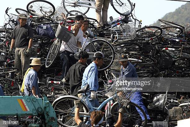 Workers on a North Korean ship pack a load of used bicycles and refrigerators at the Maizuru port October 13 2006 in Maizuru Japan The Japanese...