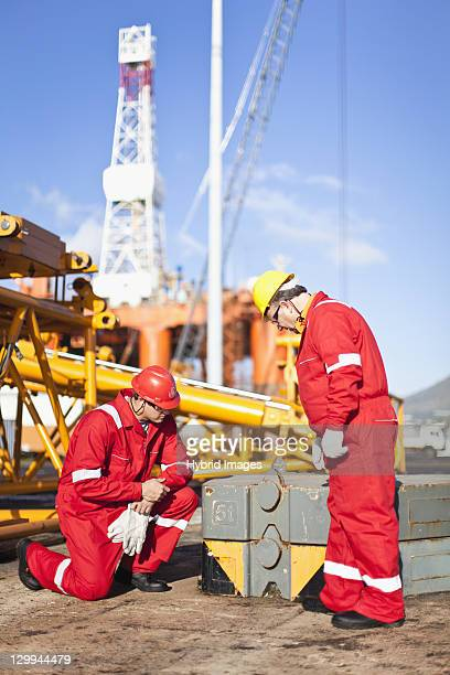 Workers on oil rig examining equipment