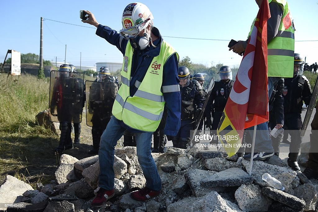 Workers on strike are evacuated by French riot policemen as they block the access to an oil depot near the Total refinery of Donges, western France, to protest against the government's planned labour law reforms, on May 27, 2016. The French government's labour market proposals, which are designed to make it easier for companies to hire and fire, have sparked a series of nationwide protests and strikes over the past three months. French unions on May 27 called on workers to 'continue and step up their action', as a wave of strikes against a disputed labour law disrupted transport and fuel supplies. / AFP / JEAN